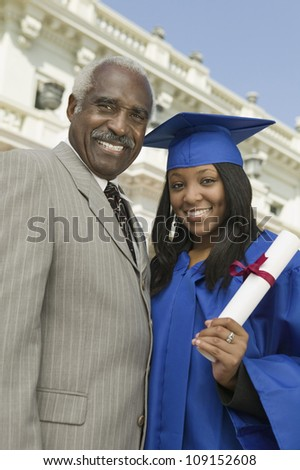 Portrait of a happy female graduate standing with father in front of the university