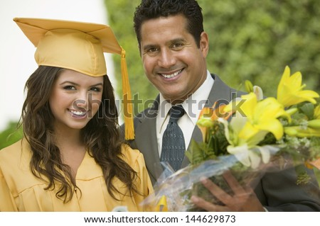 Portrait of a happy female graduate with flowers and father outside