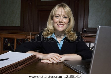 Portrait of a happy female lawyer sitting with laptop and documents in courthouse - stock photo