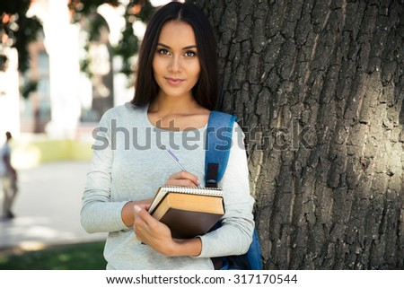 Portrait of a happy female student writing notes in notepad outdoors and looking at camera - stock photo