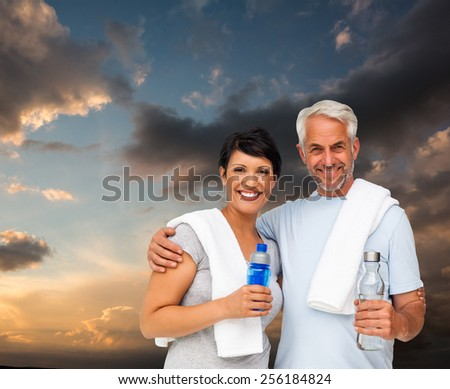 Portrait of a happy fit couple against blue and orange sky with clouds - stock photo