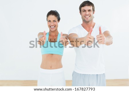 Portrait of a happy fit young couple gesturing thumbs up in fitness studio