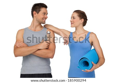 Portrait of a happy fit young couple with exercise mat and water bottle over white background - stock photo