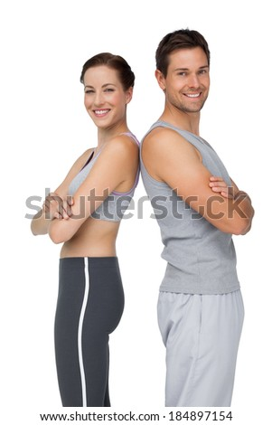 Portrait of a happy fit young couple with hands crossed over white background