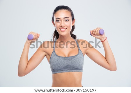 Portrait of a happy fitness woman working out with dumbbells isolated on a white background. Looking at camera