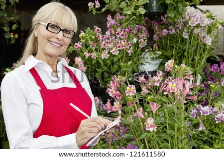 Portrait of a happy florist taking notes in greenhouse - stock photo