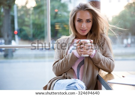 Portrait of a happy girl drinking coffee in cafe and looking at camera - stock photo
