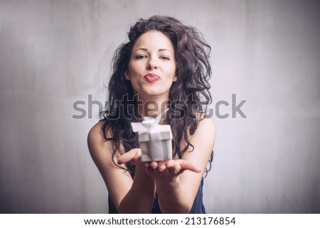 Portrait of a happy girl giving present box - stock photo