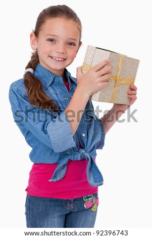 Portrait of a happy girl holding a gift box against a white background