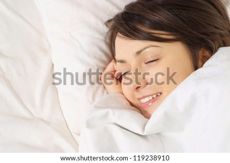 portrait of a happy girl lying in bed on a light background - stock photo