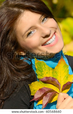 Portrait of a happy girl with golden autumn leaves in hand - stock photo