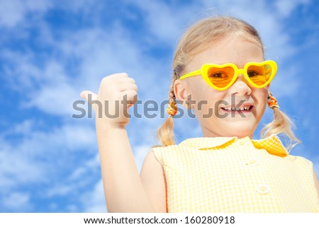 portrait of a happy girl with sunglasses against the sky