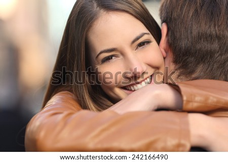 Portrait of a happy girlfriend hugging her boyfriend and looking at camera - stock photo