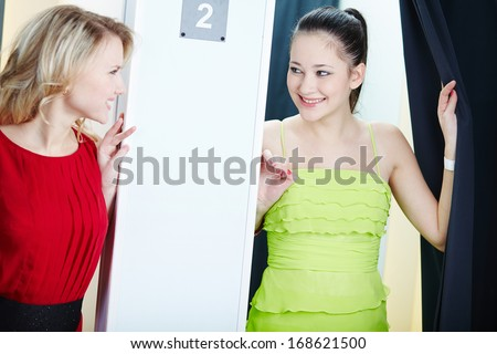 Portrait of a happy girls looking at one another in clothing department - stock photo