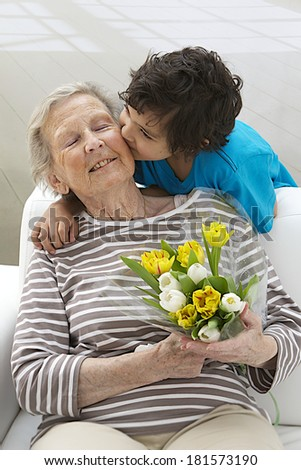 Portrait of a happy grand mother and little son embracing with flowers in the living room  - stock photo