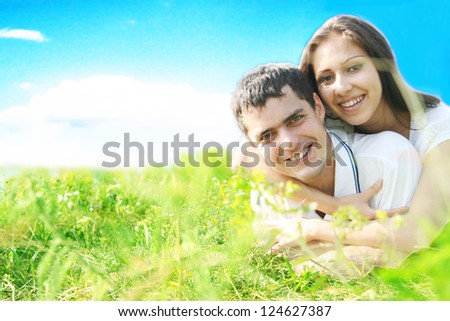 Portrait of a happy hispanic young couple lying on grass in a park - Outdoor girl lies on top of a guy in white shirt  Space for inscription