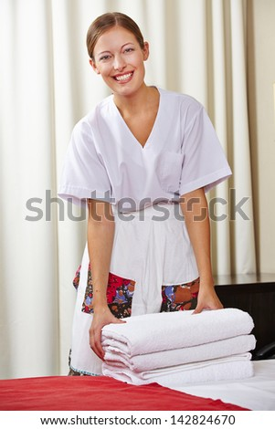 Portrait of a happy hotel maid doing housekeeping in a hotel room - stock photo