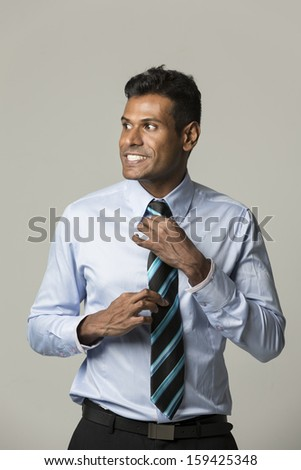 Portrait of a happy Indian business man adjusting his tie. - stock photo
