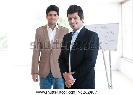 portrait of a happy Indian businessman standing in the boardroom with his colleague in the background