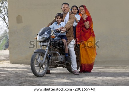 Portrait of a happy Indian family on bike - stock photo