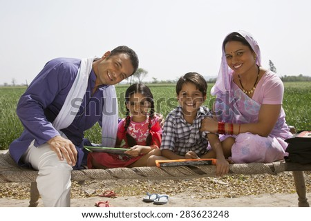 Portrait of a happy Indian family sitting on cot - stock photo