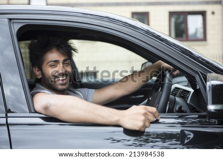 Portrait of a happy Indian man smiling in his new car.  - stock photo