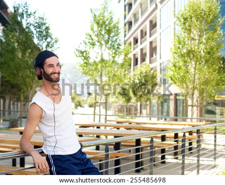 Portrait of a happy jogger relaxing with music on headphones - stock photo