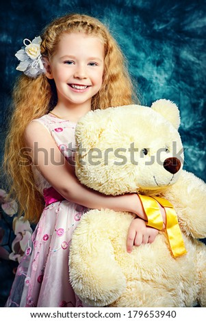 Portrait of a happy little angelic girl with her teddy bear smiling at camera. - stock photo