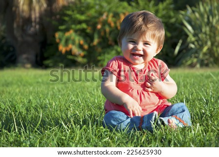 Portrait of a happy little baby in the park - stock photo