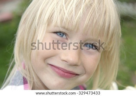 Portrait of a happy little blond girl with the focus on the right eye, shallow DOF