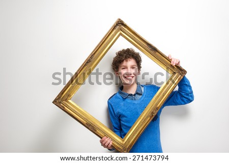 Portrait of a happy little boy holding picture frame - stock photo