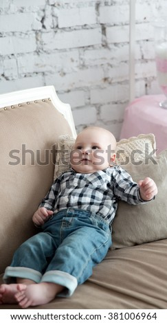 Portrait of a happy  little boy laying on the sofa wearing jeans over brick wall painted white