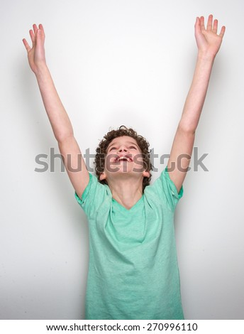 Portrait of a happy little boy smiling with hands raised - stock photo