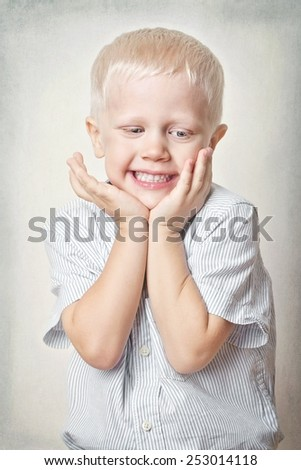 Portrait of a happy little boy with blue eyes and blond hair.Age 4 years. - stock photo