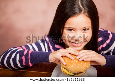 Portrait of a happy little girl eating a hamburger, shot from a high angle - stock photo