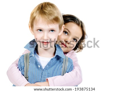 Portrait of a happy little girl embracing a cute boy. Children. Isolated over white.