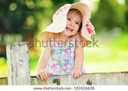 Portrait of a happy little girl in countryside at green background  - stock photo