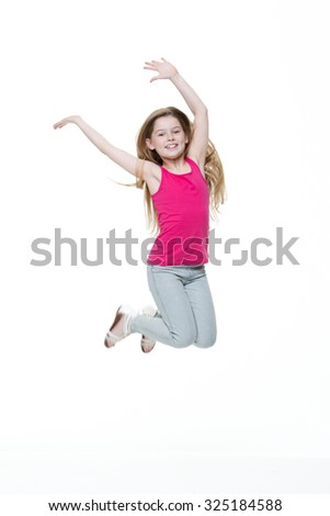 Portrait of a happy little girl jumping in the air against a white background. - stock photo