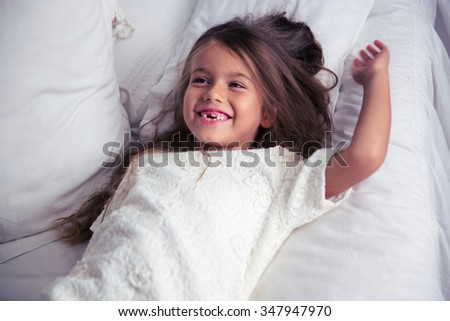 Portrait of a happy little girl lying in bed at home