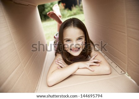 Portrait of a happy little girl lying in cardboard box