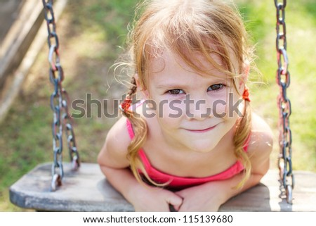 portrait of a happy little girl on a swing - stock photo