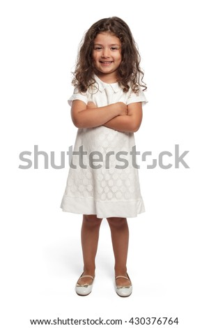 Portrait of a happy little girl on white background looking at the camera smiling arms crossed - stock photo