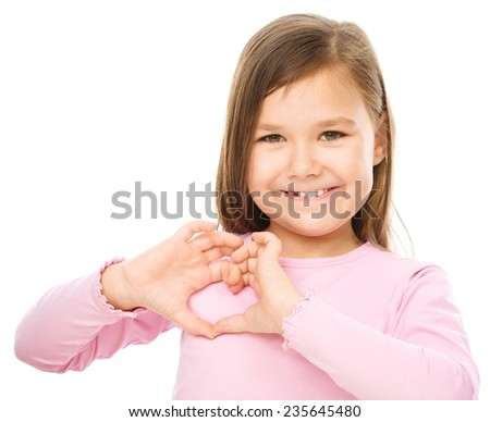 Portrait of a happy little girl showing heart gesture, isolated over white - stock photo