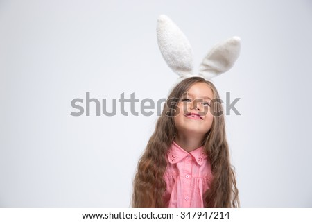 Portrait of a happy little girl with bunny ears looking up at copyspace isolated on a white background - stock photo