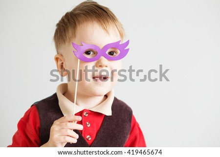 Portrait of a happy little kid in carnival mask against a white background - stock photo