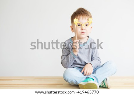 Portrait of a happy little kid in cartoon yellow paper glasses against a white background - stock photo