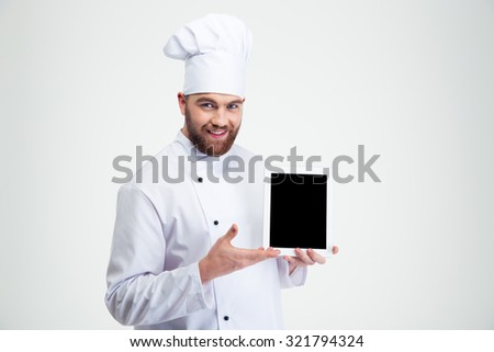 Portrait of a happy male chef cook showing blank tablet computer screen isolated on a white background - stock photo
