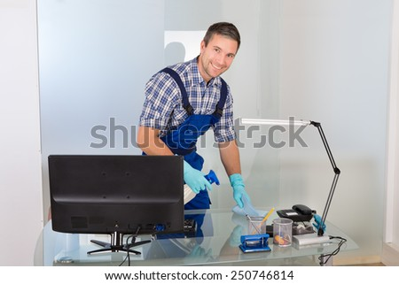 Portrait Of A Happy Male Janitor Cleaning Desk In Office