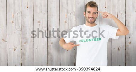 Portrait of a happy male volunteer pointing to himself against wooden background