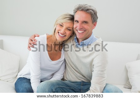 Portrait of a happy man and woman sitting in living room at home